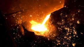 Pouring of liquid metal in open hearth workshop of the metallurgical plant. Stock footage. Smelting of the metal in the. Pouring of liquid metal in open hearth royalty free stock photos