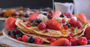 Pouring maple syrup over a breakfast of pancakes with berries and dry fruits. Defocused background stock photos