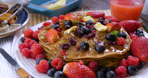 Pouring maple syrup over pancakes with berries and dry fruits. Pouring maple syrup over a breakfast of pancakes with berries and dry fruits royalty free stock images