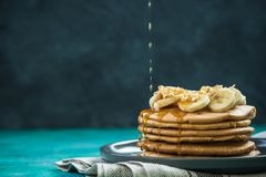 Pouring maple syrup over pancakes pile. Copy space image stock images