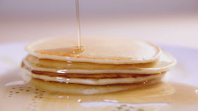 Pouring maple syrup on pancakes, slow motion stock footage