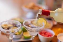 Pouring a margarita into glass. Pouring a margarita into a glass with salt on cinco de mayo stock photos