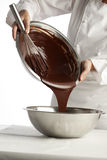 Pouring melted chocolate into a metal bowl Stock Images