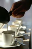 Pouring milk. Close-up of hand holding pot and pouring warm milk into white coffee cup with golden rim Stock Image