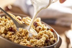 Pouring milk in a bow of organic hazelnut granola stock images