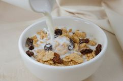Pouring Milk In Bowl of Cereal and Raisin for Breakfast Meal. Royalty Free Stock Image