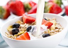 Pouring milk into bowl of cereals Royalty Free Stock Photography