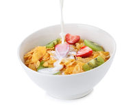 Pouring milk into bowl of corn flakes with fruit Stock Image