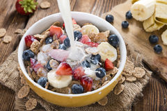 Pouring Milk in a bowl with Cornflakes and Fruits Royalty Free Stock Images