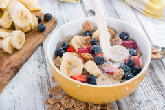 Pouring Milk in a bowl with Cornflakes and Fruits Stock Photos