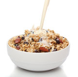 Pouring milk into a bowl with granola Royalty Free Stock Image