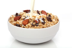 Pouring milk into a bowl with granola Royalty Free Stock Photo
