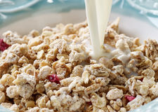 Pouring milk into bowl of muesli Stock Photography