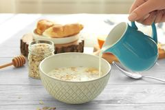 Pouring milk into bowl with oatmeal for breakfast Royalty Free Stock Images