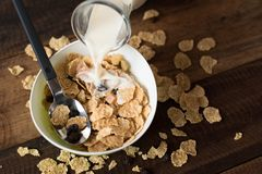 Pouring milk into breakfast cereal  cornflakes. Healthy eating concept Royalty Free Stock Photos