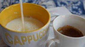 pouring milk in a cappuccino cup stock video footage