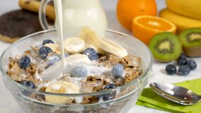 Pouring milk on cereals flakes and fruits for breakfast in slow motion stock video