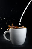 Pouring milk into coffee Stock Photography