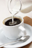 Pouring milk into coffee. Pouring milk into a cup of black coffee Stock Images