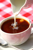 Pouring milk into coffee. Photograph of milk being poured into coffee on an outside table Stock Image