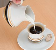 Pouring milk into coffee Royalty Free Stock Image