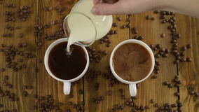Pouring milk into coffee cups. Pouring milk into two coffee cups on a wooden table stock video