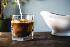 Pouring milk and coffee in a glass royalty free stock photography