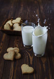 Pouring milk with cookies in the shape of a heart Royalty Free Stock Images