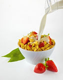 Pouring milk in cornflakes bowl with strawberries Royalty Free Stock Image
