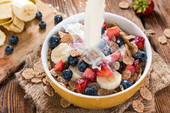 Pouring Milk on Cornflakes with fresh Fruits Royalty Free Stock Photos