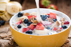 Pouring Milk on Cornflakes with fresh Fruits Royalty Free Stock Images