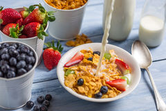 Pouring milk into cornflakes with fruits Stock Photos