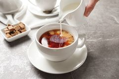 Pouring milk into cup of black tea. On table stock photos