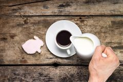 Pouring milk in Cup of Coffee. Coffee with gingerbread rabbit on wood background. Top View Stock Photo