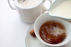 Pouring milk into cup of tea. Royalty Free Stock Images