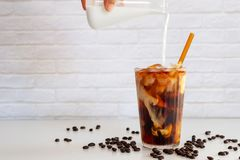Pouring milk into a glass of homemade cold brew coffee on white. Table royalty free stock photos