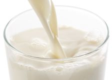 Pouring milk into glass royalty free stock photography