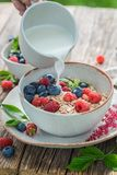 Pouring milk into granola with fresh blueberries and raspberries. On old wooden table Stock Photos