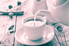 Pouring milk from jug cup black coffee Royalty Free Stock Photography