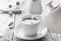 Pouring milk from jug cup black coffee Royalty Free Stock Images