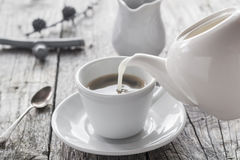 Pouring milk from jug cup black coffee Royalty Free Stock Photo