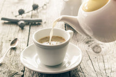 Pouring milk from jug cup black coffee Royalty Free Stock Image