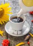 Pouring milk from jug cup black coffee Stock Photography