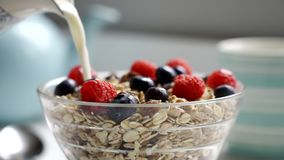 Pouring milk from jug onto bowl of healthy breakfast muesli stock footage