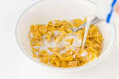 Pouring milk onto a bowl of cereal Royalty Free Stock Images