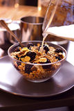 Pouring milk over cornflakes with blackberries Royalty Free Stock Photos