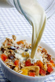 Pouring milk over muesli with dried fruit Royalty Free Stock Photos