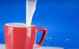 Pouring milk into a red cup Stock Image