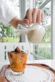 Pouring milk on Thai Tea ice cube Royalty Free Stock Photos