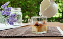 Pouring milk to make ice caffe latte. Making ice cafe latte by pouring milk into espresso ice cube Royalty Free Stock Image